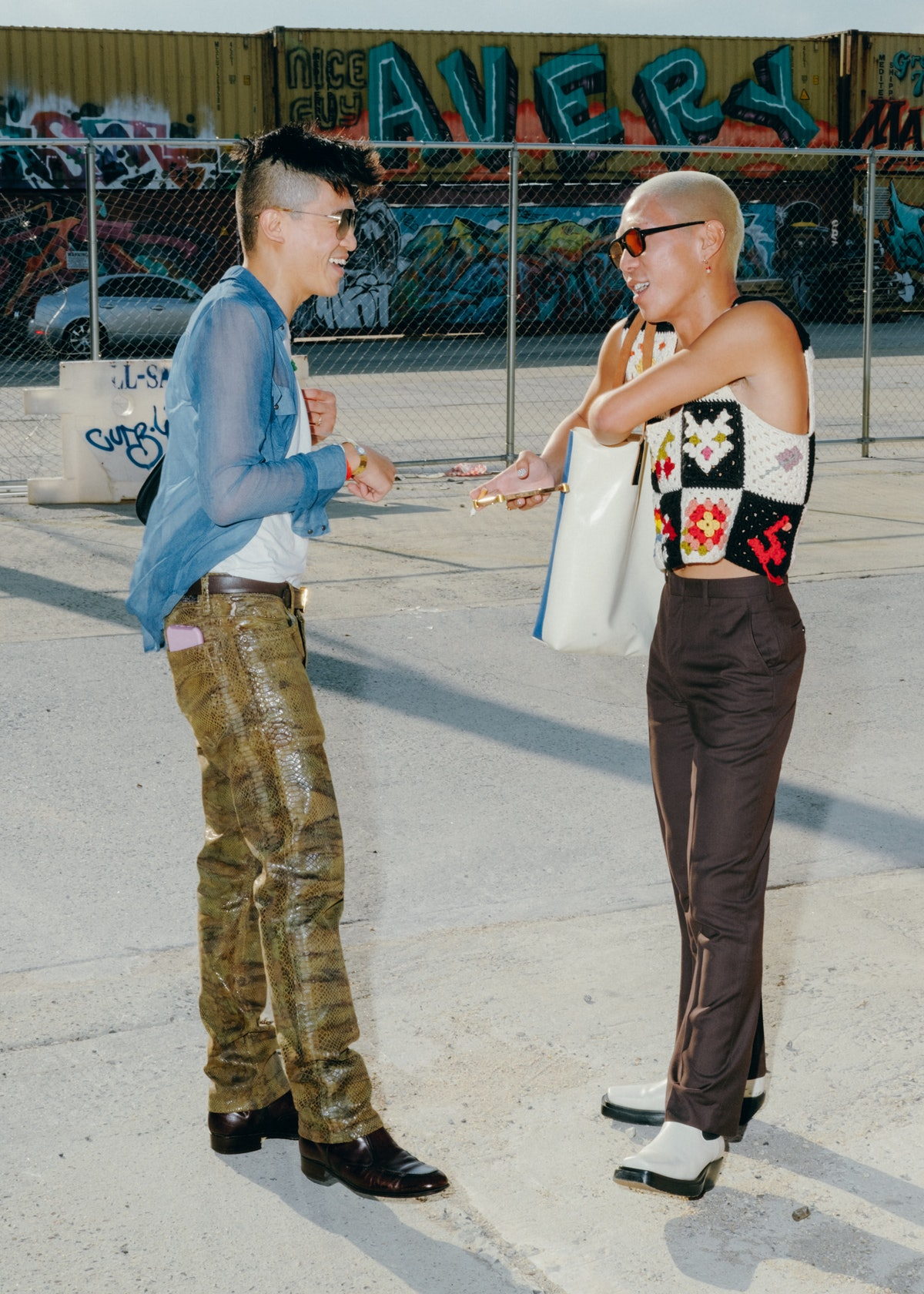 Two friends are talking in the street.  Both wear tight pants and shirts.