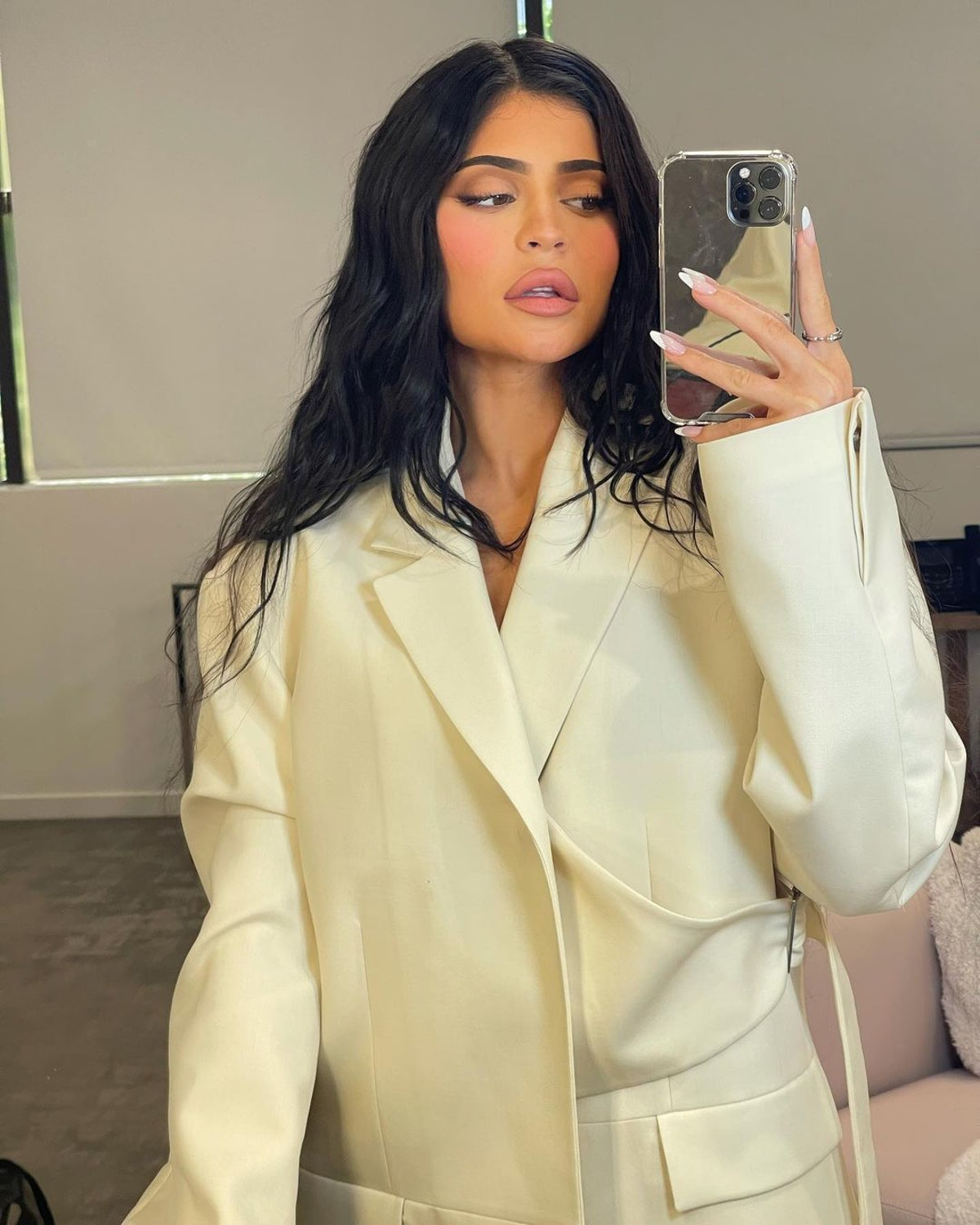 Kylie Jenner poses in a mirror selfie wearing a white blazer.