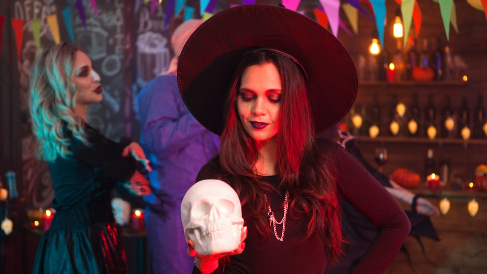 Thoughtful young woman in halloween costume looking at her human skull. Halloween costume.