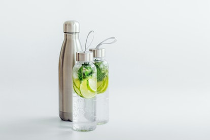 Fresh lime and mint infused water, cocktail, detox drink, lemonade in reusable bottles. Summer drinks. Health care concept.