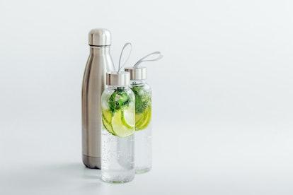 Fresh lime and mint infused water, cocktail, detox drink, lemonade in reusable bottles. Summer drink...