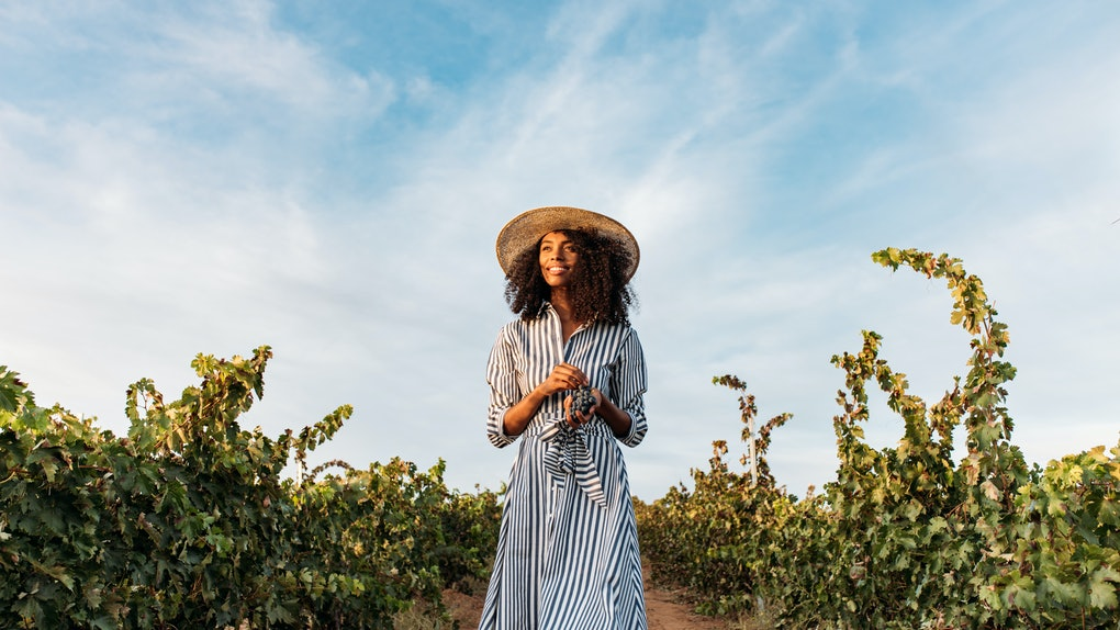 Young woman in a straw hat walking in a path in the middle of a vineyard with a bunch of grapes in hands