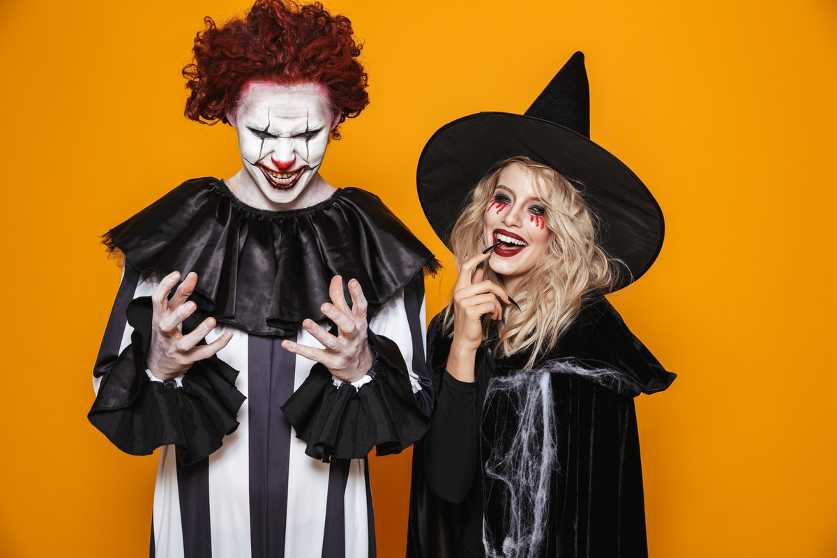 Image of witch woman and clown man wearing black costume and halloween makeup smiling at camera isolated over yellow background