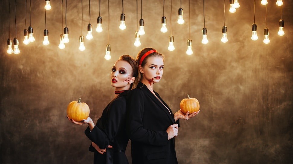 Two happy young women in black witch halloween costumes on dark background