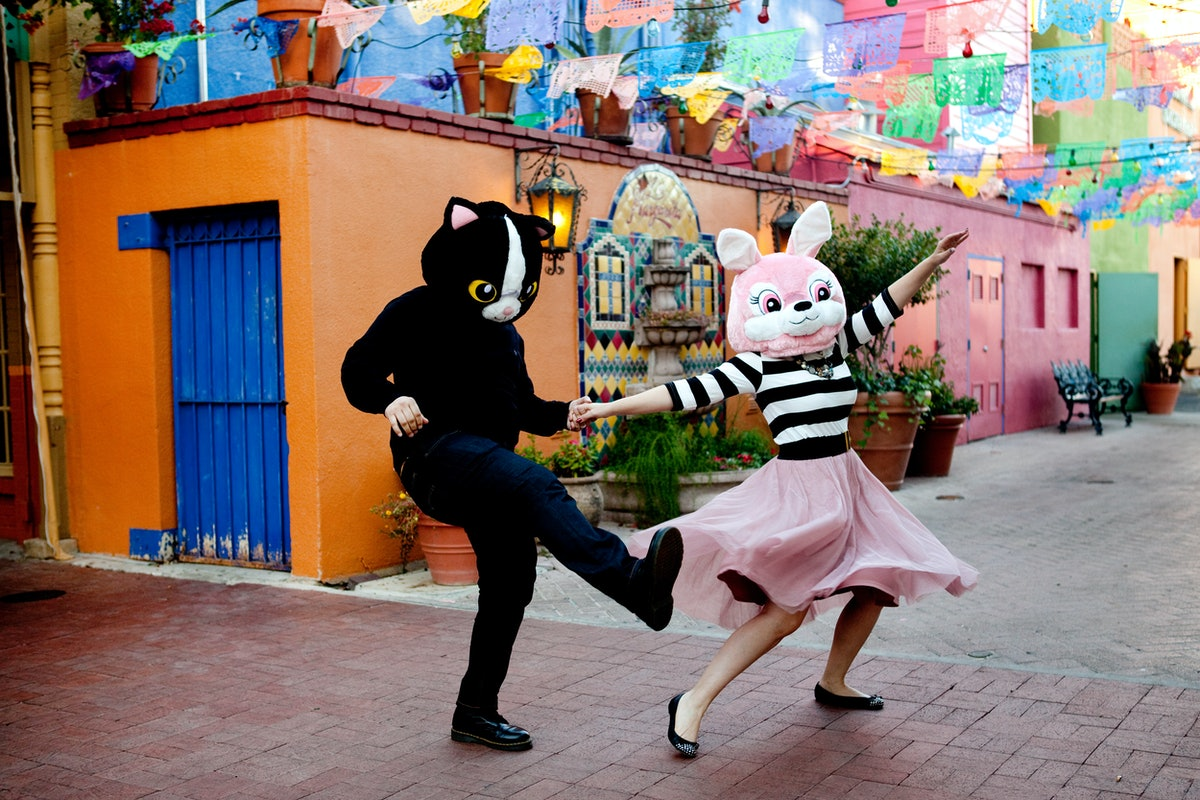 Couple wearing cat heads, holding hands, spinning and dancing in front of colorful buildings, and flags in downtown San Antonio, TX near the Mexican Market, La Villita and the Riverwalk. Fiesta.