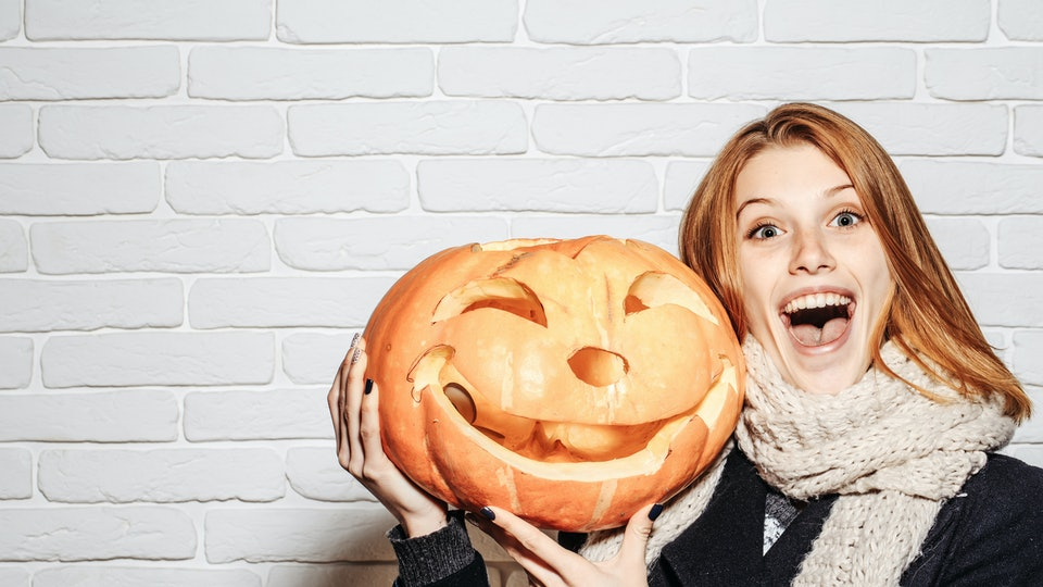 Halloween woman with happy face. Party and traditional food. Woman in coat and scarf at brick wall. Girl with orange scary pumpkin. Holiday and celebration, copy space