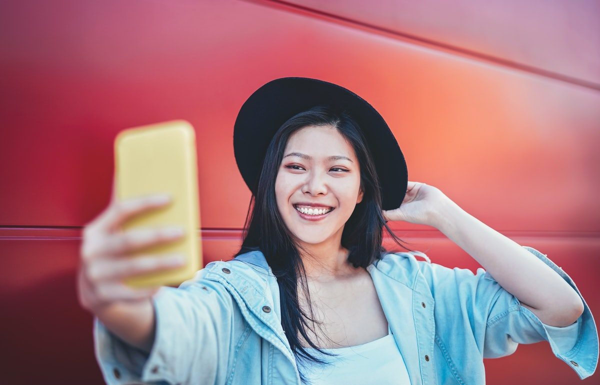 A happy woman in a black hat takes a selfie in front of a red wall.