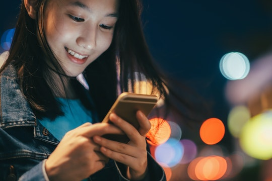 Young woman traveler using mobile phone searching GPS. Teen girl using mobile phone to chat and send...