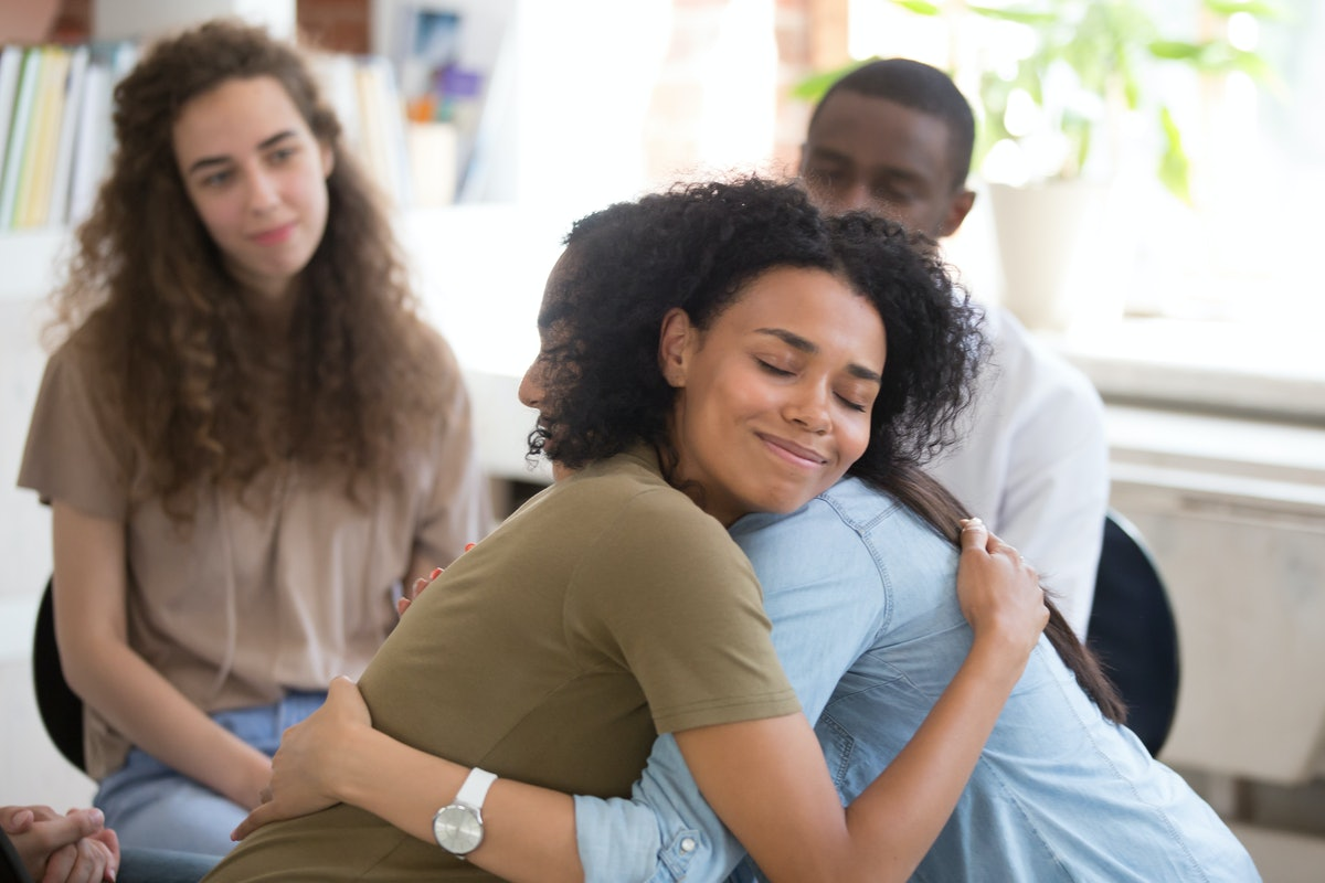 African American and Asian women embracing at group therapy session, empathy concept, psychological support, diverse friends overcome problem together, addiction treatment or team building close up