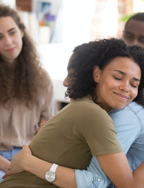 African American and Asian women embracing at group therapy session, empathy concept, psychological ...
