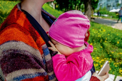 little baby-girl falls asleep on mom's chest on a sunny day