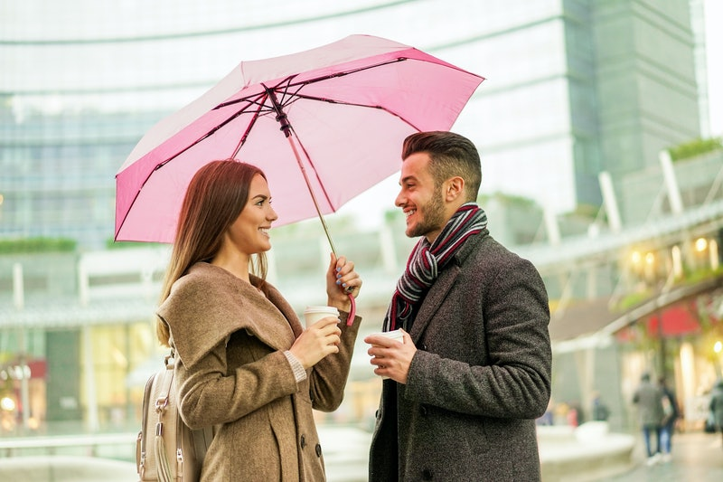 Young couple of lovers with coffee take away paper cup under a umbrella in city center - Handsome people having fun in city urban center in a raining day - Love and vacation concept - Warm filter