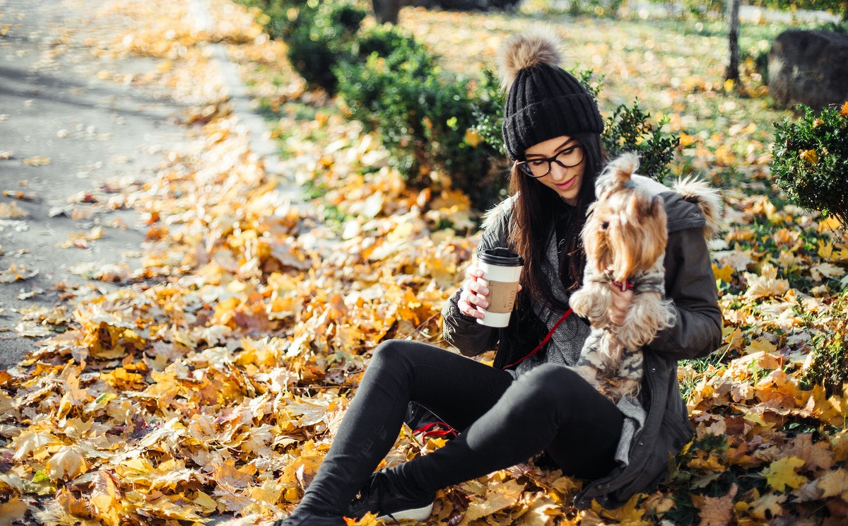 A young woman sits with her dog while drinking a latte in the fall in a pile of yellow leaves.
