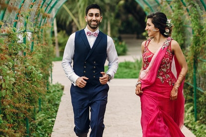 Indian newlyweds run under green arch in the garden. If you're alcohol-free, weddings can be challenging, but still rewarding.
