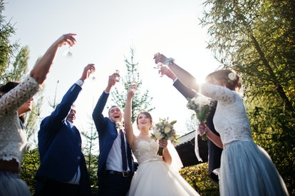 Wedding couple and groomsmen with bridesmaids drinking outdoors in the park. If you're sober at a wedding, finding an accountability partner can help.