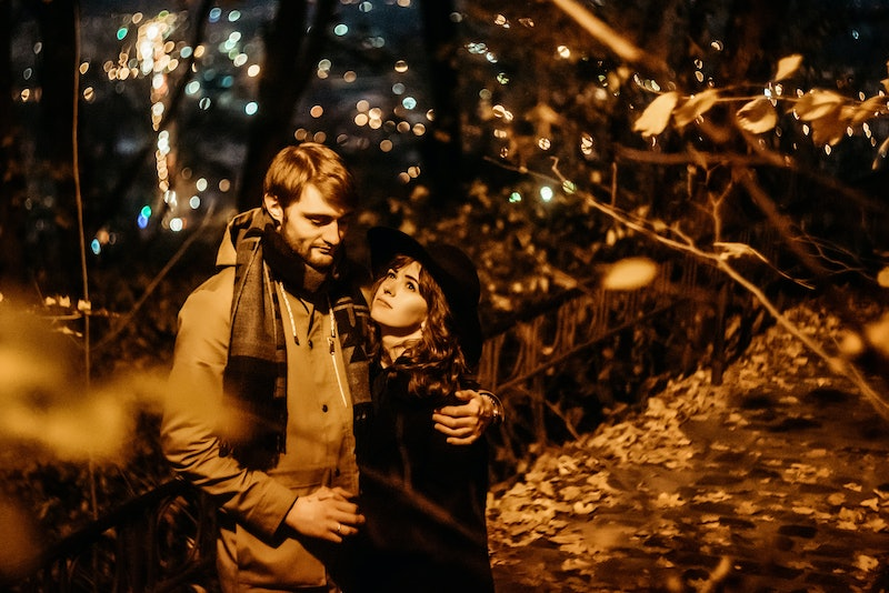 happy stylish couple hugging and holding hands with tender under yellow lantern  in night lights of the city