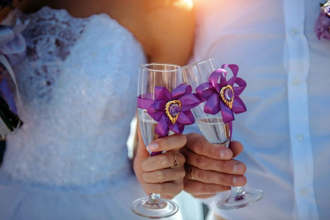 Bride and groom holding glasses of sparkling water in their hands, close-up. If you're not drinking at a wedding, finding fun beverages can bring you into the party.