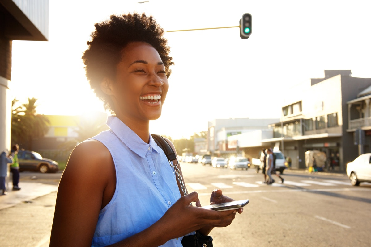 Close up portrait of attractive woman with mobile phone looking away and laughing on the city street