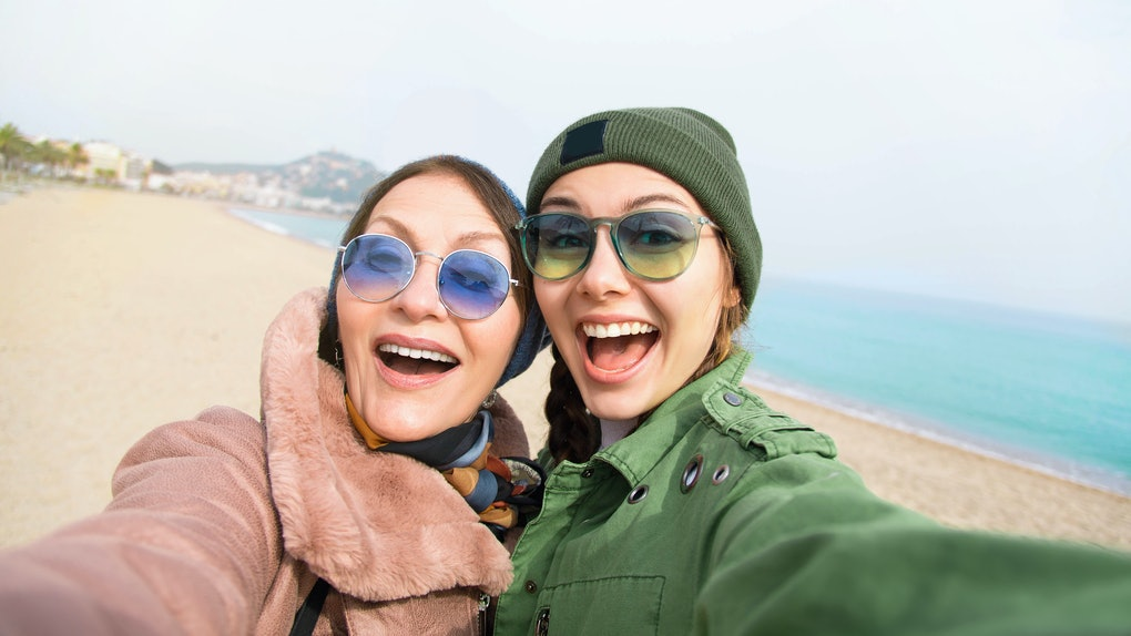 Daughter poses with mom for selfie on the beach while traveling.