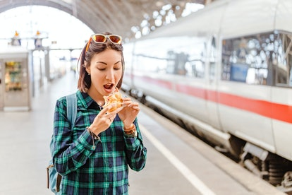 Healthy young woman biting her hamburger at railway station near fast train