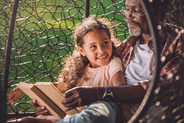 smiling african american granddaughter reading book while sitting in swinging hanging chair with grandfather