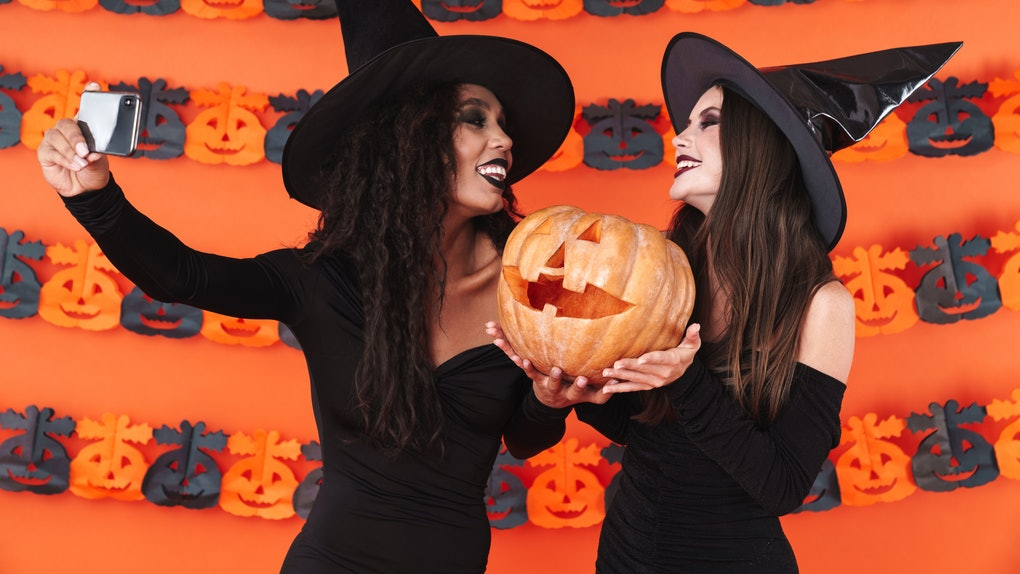 Image of beautiful witch women in black halloween costume taking selfie photo on cellphone with pumpkin isolated over orange wall