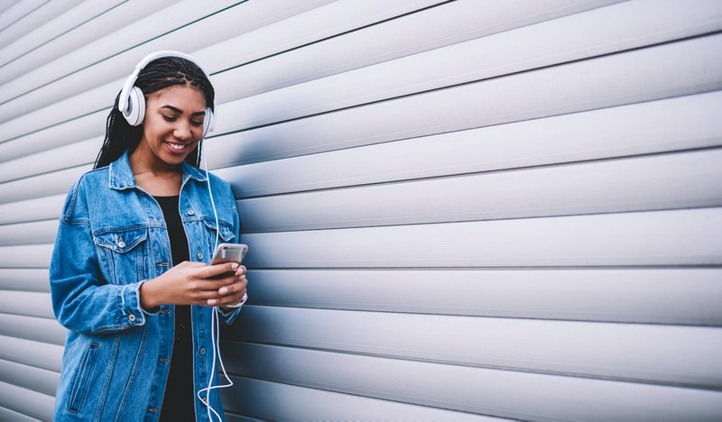 Happy smiling woman enjoying positive audio book via headphones during communicating with friends on smartphone device, cheerful hipster girl listening music during installing media app on cellular