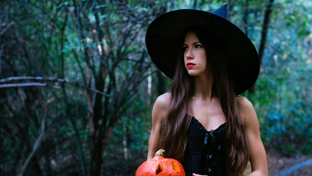 Halloween holiday background. Halloween Witch with a halloween pumpkin jack o lantern decor with funny face in a dark forest. Beautiful young woman in witches hat and costume holding pumpkin.