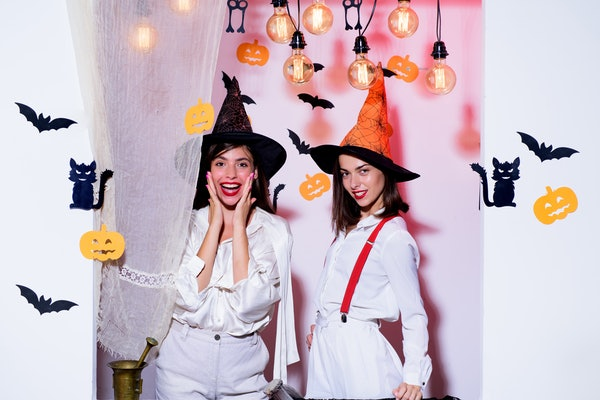 Emotional young women in halloween costumes on halloween party. Surprise. Halloween girls through hole in white wall. Best friends girls celebrates thanks giving day. Halloween copy space