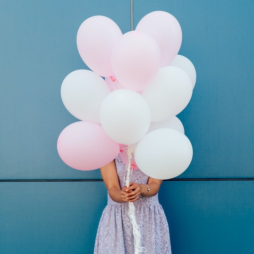 Young woman hiding her face with bunch of balloons, standing against blue wall. Dressed in tender dress. Outdoors.
