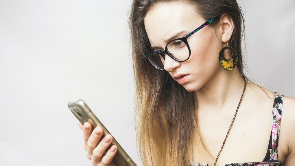 Surprised sad young woman looking in phone
