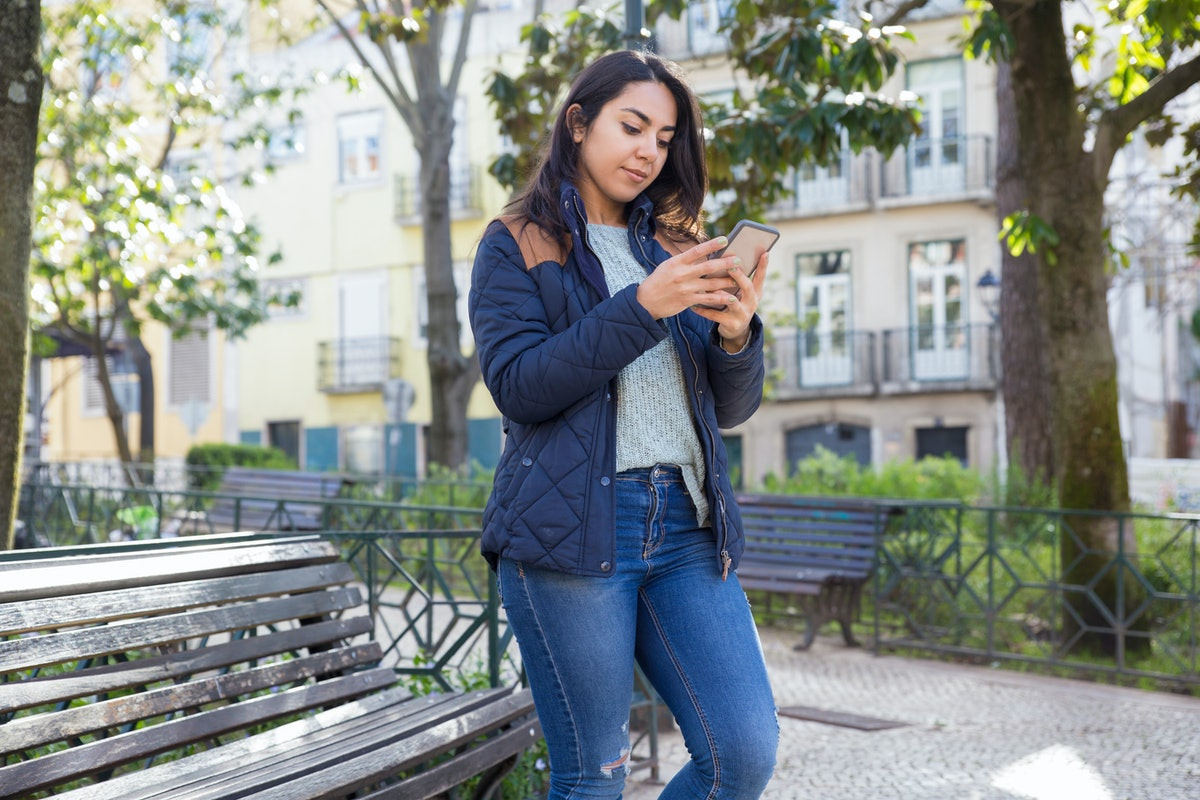 Serious woman using smartphone and standing outdoors. Pretty young lady wearing jacket with trees and buildings in background. Urban lifestyle and communication concept.