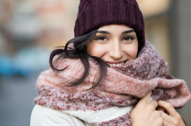 Closeup face of a young happy woman enjoying winter wearing scarf and cap. Smiling girl in a colorful shawl looking at camera. Latin woman with knitted bordeaux hat and woolen scarf.
