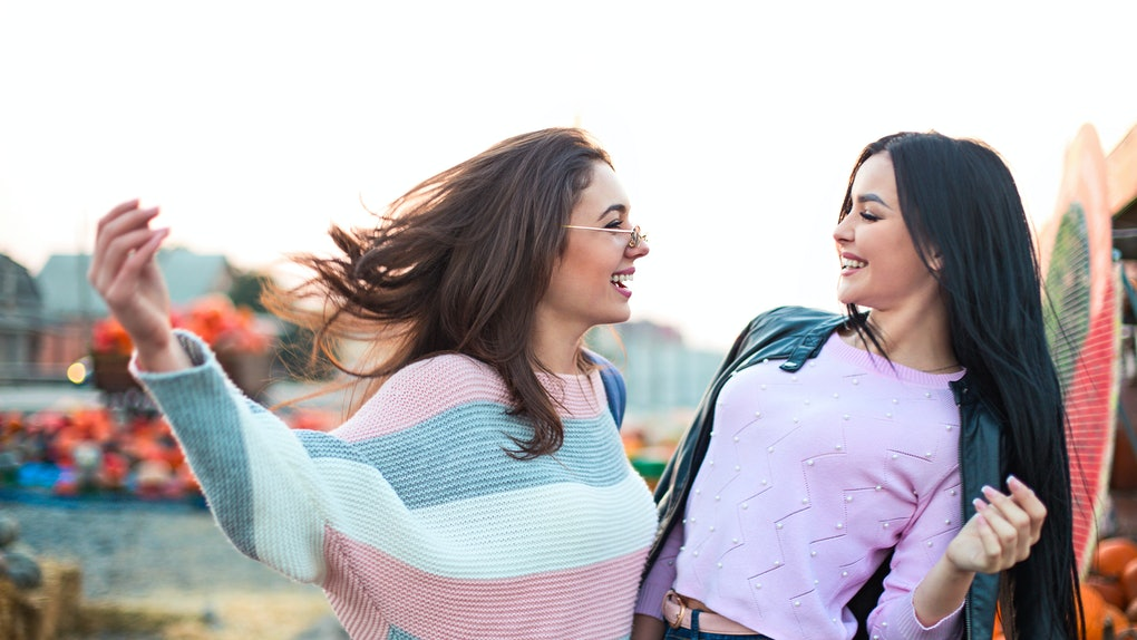 Instagram captions for pumpkin patch photos are perfect for these two young women laughing and looking at each other in a pumpkin patch.