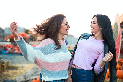 Instagram captions for pumpkin patch photos are perfect for these two young women laughing and looki...