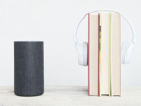 Smart speaker Amazon Alexa Echo device on the left next to some books and hearphones against a white background. Empty copy space for Editor's text