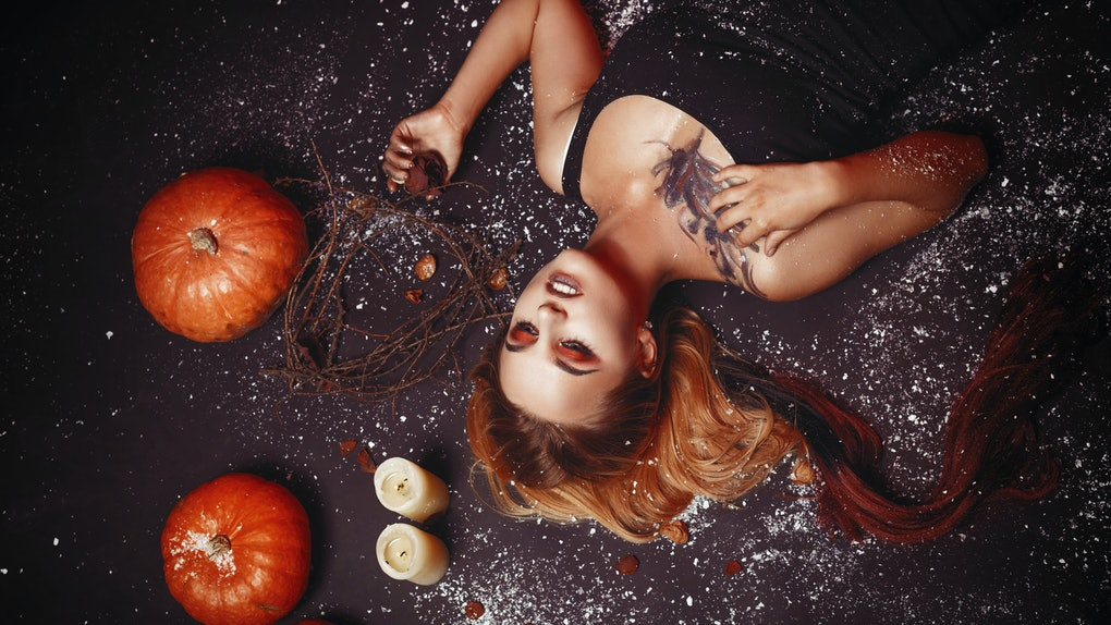 Halloween concept, girl vampire with red eyes red lips lying on floor with pumpkins and snow around. Scary crazy woman trick or treat time. Female makeup for holiday with candle