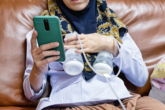 Busy mother playing phone while using automatically electric breast pump feeding for her baby.