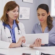 Senior medical physician using tablet to share lab results with young patient