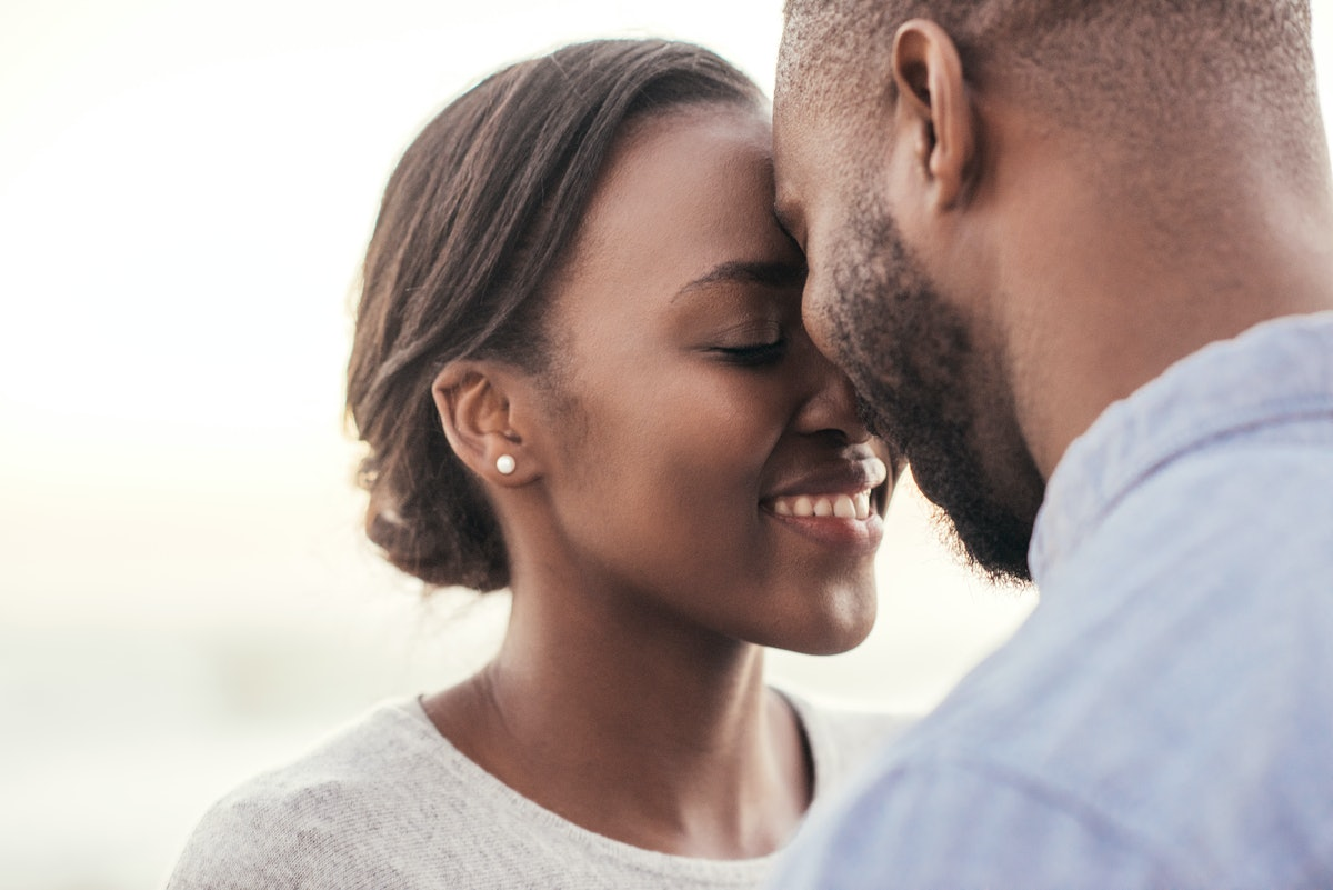 Smiling young African couple standing face to face with their eyes closed while enjoying a romantic ...