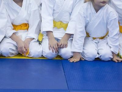 Kids in yellow belts sitting on a blue mat in karate class