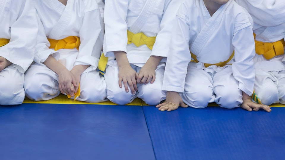 Kids in yellow belts sitting on a blue mat in karate class