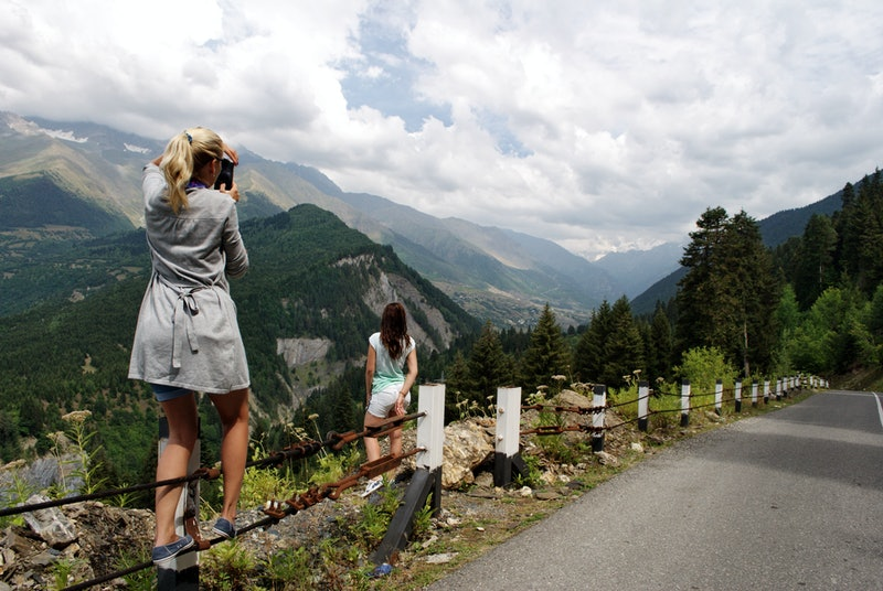 A young beautiful girl photographs her friend on the phone against the backdrop of a beautiful landscape high in the mountains