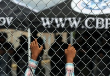A migrant leans on a fence of the Gateway International Bridge that connects downtown Matamoros, Mex...