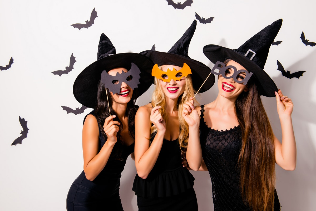 Group of three diverse charming coquettes in dark masquerade elegant dresses, masks on eyes, smiling, enjoying near decorated wall with bats, toothy beaming smiles, scary bright cosmetics hot figures
