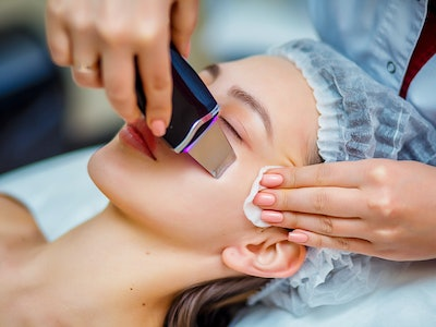 Woman receiving ultrasonic facial exfoliation at cosmetology salon. Procedure clearing clogged pores...