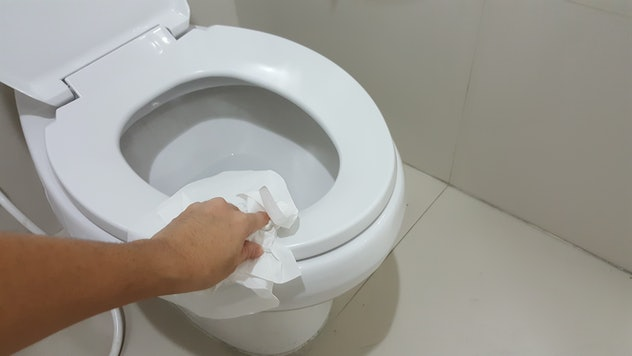 Human's hand wipe the toilet seat cover clean with tissue paper.