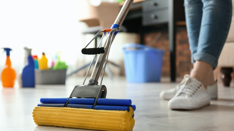 Woman cleaning floor with mop in living room for flu season