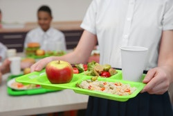 Student holds lunch tray in cafeteria.