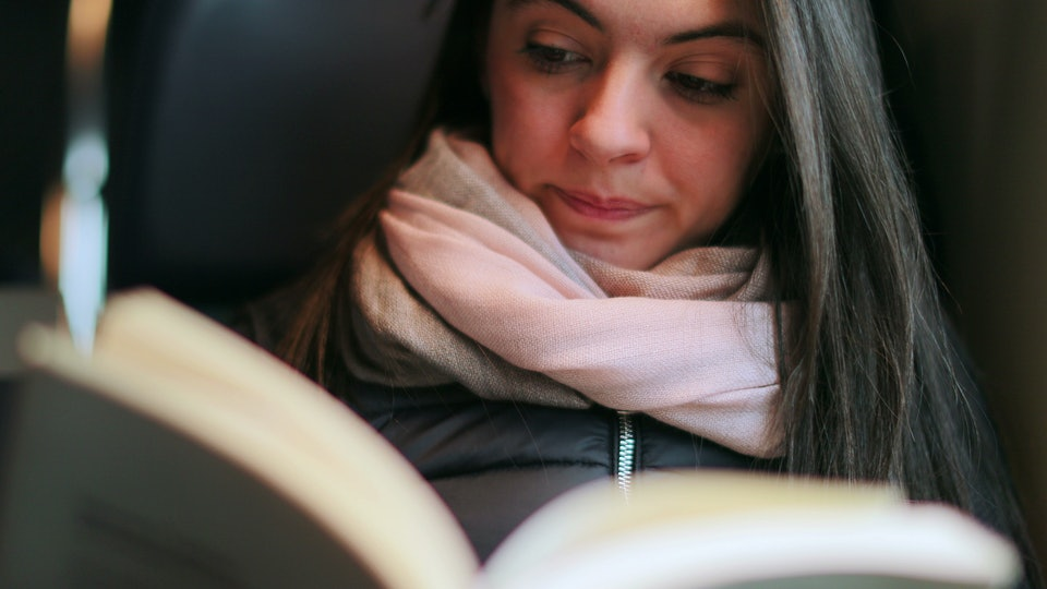 Woman reading book while commuting by train
